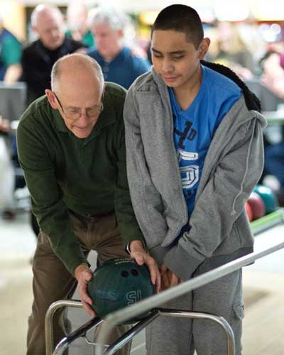 picture of Dennis Gish helping student at school for the blind bowling night