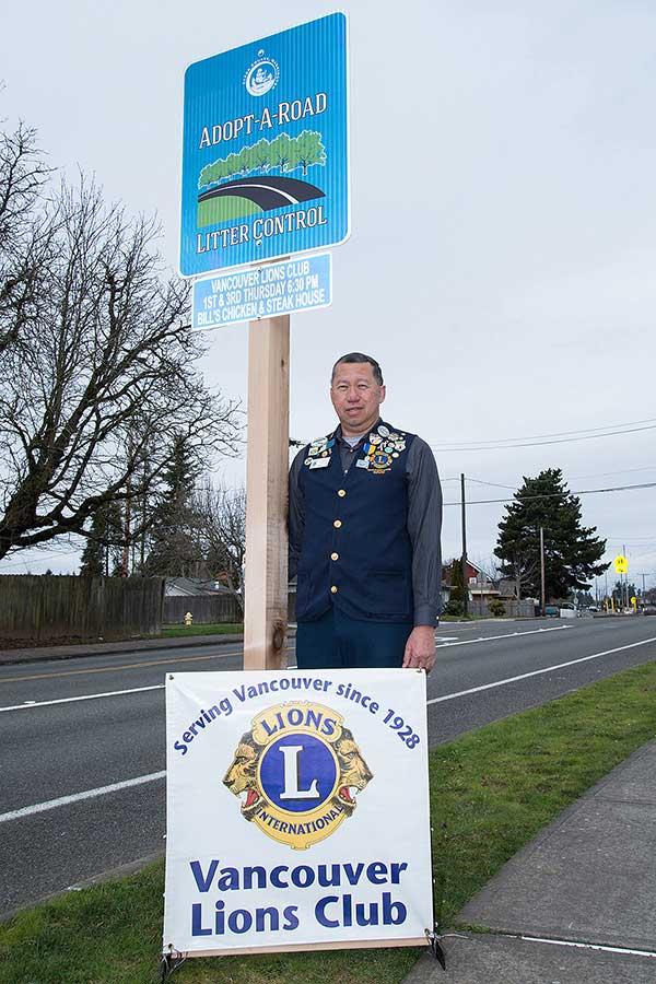 picture of Wade Enos standing next to adopt a road sign